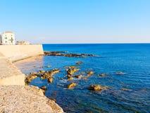 Vista del mar y un fragmento de las paredes de la defensiva de Alghero Cerdeña, Italia Fotografía de archivo libre de regalías