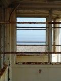 Vista del mare attraverso un riparo abbandonato arrugginito della spiaggia Immagine Stock