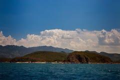 vista del mare azzurrato delle isole collinose contro i cumuli del cielo blu Immagini Stock