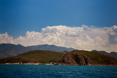 vista del mare azzurrato delle isole collinose contro i cumuli del cielo blu Fotografia Stock