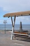 Vista del mare con il banco ed il piccolo faro Immagini Stock Libere da Diritti