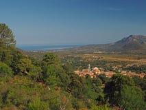 Vista del mare con la collina del villaggio e gli alberi verdi fotografie stock libere da diritti