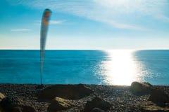 Vista del mare con la vela per fare windsurf sulla spiaggia Fotografie Stock Libere da Diritti
