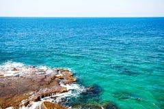 Vista del mare o dell'oceano con acqua e le pietre del turchese Immagini Stock