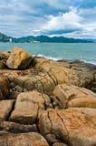 Vista del mare sul piccolo stabilimento dall'isola di grandi rocce Fotografie Stock
