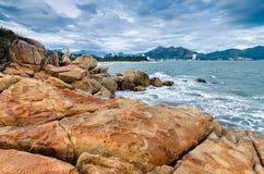 Vista del mare sul piccolo stabilimento dall'isola di grandi rocce Fotografia Stock Libera da Diritti