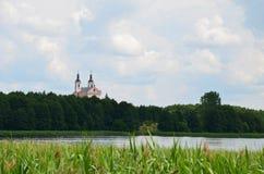 Vista del monastero da una barca - lago e foresta al giorno soleggiato fotografie stock libere da diritti