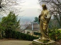 Vista del nuvoloso, inverno Lione da un percorso della montagna con una statua bronzea nella priorità alta, Francia immagini stock