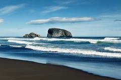 Vista del Océano Pacífico, de la isla en el océano y de la playa con la arena volcánica negra Kamchatka, Extremo Oriente Imagenes de archivo