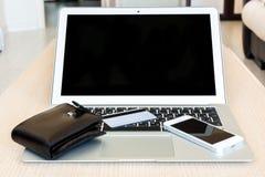 Vista del ordenador portátil con la tarjeta, la cartera y el teléfono de crédito Imágenes de archivo libres de regalías