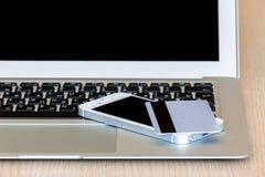 Vista del ordenador portátil con las tarjetas y el teléfono de crédito Fotos de archivo