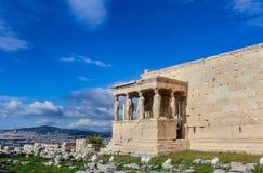 Vista del pórtico de las cariátides en el templo de Erechtheion en la Atenas Accropolis con vistas a Atenas y montañas en fotografía de archivo libre de regalías