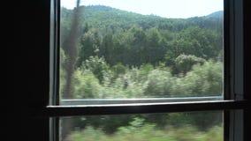 Vista del paesaggio dalla finestra del treno commovente stock footage