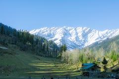 Vista del paesaggio della valle con la montagna della neve nel fondo e la casa greenfiled e di legno in priorità alta fotografia stock libera da diritti