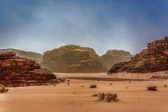 Vista del paisaje del desierto debajo de los cielos nebulosos azules Foto de archivo