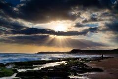 Vista del paisaje tropical de la playa rocosa en la salida del sol Imagen de archivo