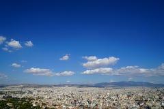 Vista del paisaje urbano de Atenas que muestra edificios blancos de cintura baja, la montaña, árboles, la nube blanca y el fondo  Imagenes de archivo