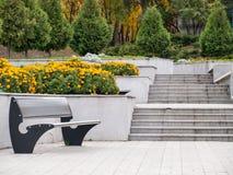 Vista del parque con las escaleras del banco y de la piedra Fotografía de archivo