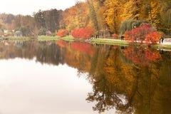 Vista del parque otoñal con la reflexión de la gente y de los árboles en el agua Fotos de archivo