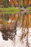 Vista del parque otoñal con la reflexión de la gente y de los árboles en el agua Fotos de archivo libres de regalías