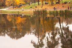Vista del parque otoñal con la reflexión de la gente y de los árboles en agua Imagen de archivo