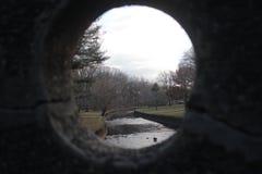 Vista del parque a través de la ventana redonda fotos de archivo libres de regalías