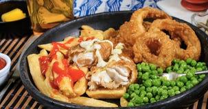 Vista del pescado frito con patatas fritas ingleses con los guisantes de jardín y la salsa de tártaro Imagen de archivo libre de regalías
