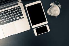 Vista del piano d'appoggio con il computer portatile, compressa, telefono cellulare Immagine Stock