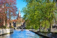 Vista del ponte e del canale, barca con i turisti, torre di chiesa a Bruges, Belguim Fotografia Stock Libera da Diritti