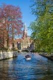 Vista del ponte e del canale, barca con i turisti, torre di chiesa a Bruges, Belguim Fotografia Stock