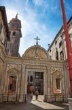 Vista del portal tallado iglesia con la gente que se va y del resplandor del sol en Venecia Fotos de archivo