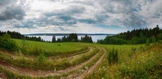 Vista del prado verde con un camino de tierra que lleva abajo de la remolque de la cuesta Imágenes de archivo libres de regalías