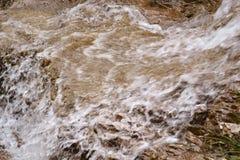 Vista del primo piano ad acqua pura che entra sulle rocce nelle montagne immagine stock