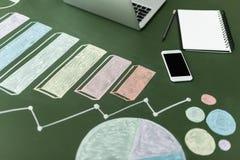 Vista del primo piano dei grafici di affari e del computer portatile con il taccuino e lo smartphone fotografie stock
