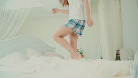 Vista del primo piano dei pigiami d'uso della gamba felice della giovane donna s, saltante sul suo letto nella mattina Movimento  archivi video