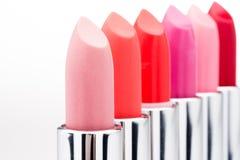 Vista del primo piano dei rossetti alla moda nei colori rossi e rosa in una fila Immagini Stock