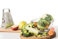 vista del primo piano dei taglieri, della grattugia, della ciotola, delle mele, della carota, dei broccoli e del cavolfiore sulla immagini stock libere da diritti