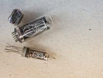 Vista del primo piano dei tubi differenti del nixie sul fondo della carta del mestiere Fotografia Stock Libera da Diritti