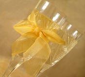 Vista del primo piano dei vetri di Champagne con l'arco su priorità bassa dorata Immagine Stock