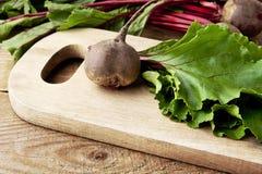 Vista del primo piano della bietola, delle foglie e delle barbabietole su minestra sul tagliere Immagini Stock