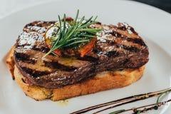 vista del primo piano della bistecca di manzo succosa deliziosa con i rosmarini ed il pane arrostito fotografia stock libera da diritti