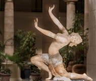 Vista del primo piano della figura di marmo del ballerino delle donne, stante contro il fondo interno scuro Fotografie Stock Libere da Diritti