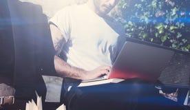 Vista del primo piano della maglietta bianca d'uso del giovane che si siede sul banco e che lavora al taccuino Studiando all'univ Fotografie Stock