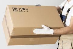 Vista del primo piano della scatola di cartone in mani del motore La rilocazione fornisce un servizio all'uomo in uniforme con la immagini stock