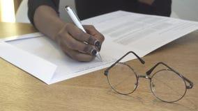 Vista del primo piano della scrittura africana della mano qualcosa nella parte anteriore degli occhiali 4K video d archivio