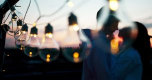 Vista del primo piano della serie di luci ai precedenti vaghi delle coppie amorose bacianti durante il tramonto video d archivio