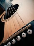 Vista del primo piano delle corde della chitarra acustica e del ponte Fotografia Stock