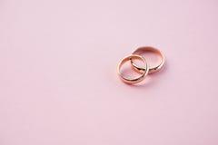 Vista del primo piano delle fedi nuziali dorate brillanti sul rosa Fotografia Stock Libera da Diritti