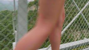 Vista del primo piano delle gambe femminili bianche di sport in scarpe atletiche che raggiungono attraverso il ponte sospeso dell archivi video