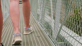 Vista del primo piano delle gambe femminili bianche di sport in scarpe atletiche che raggiungono attraverso il ponte sospeso dell video d archivio